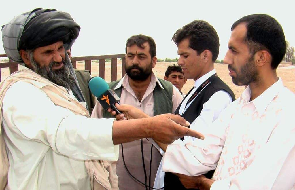 A reporter for RFE/RL's Afghan Service interviews a citizen in Helmand, Afghanistan.