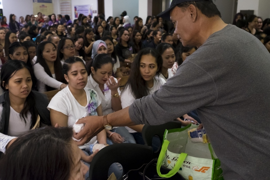 An embassy volunteer hands out meals to Filipina domestic workers who have sought refuge at the embassy after fleeing abusive employers.Credit:Alisa Reznick/PRI